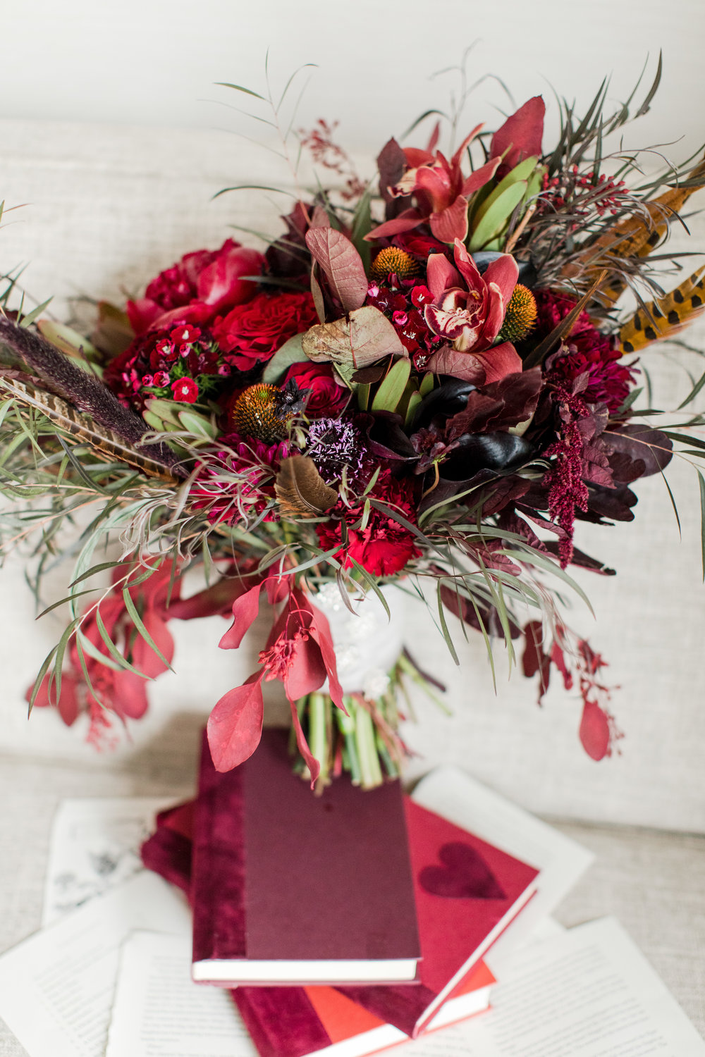 unique black and dark red bridal bouquet atop stack of books for a fall library inspired wedding photographed by jaye kogut