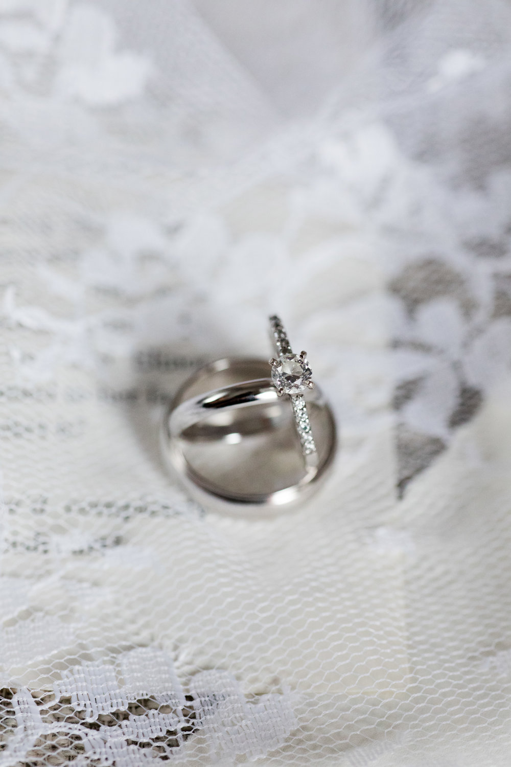 wedding bands and heirloom engagement ring from ford jewelers atop lace photographed by jaye kogut
