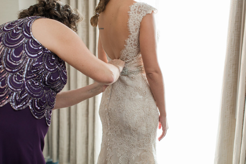 mom buttoning low back lace allure bridal gown with buttons photographed by jaye kogut