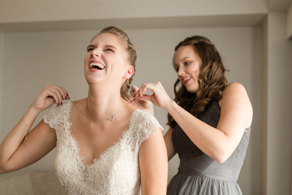 sister helps bride in lace allure bridals gown with necklace while getting ready photographed by jaye kogut