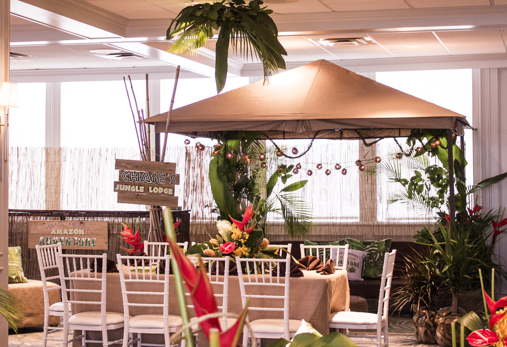 kids lounge for amazon jungle themed mitzvah at channel club with cabana lounge and rustic signs and tropical plants