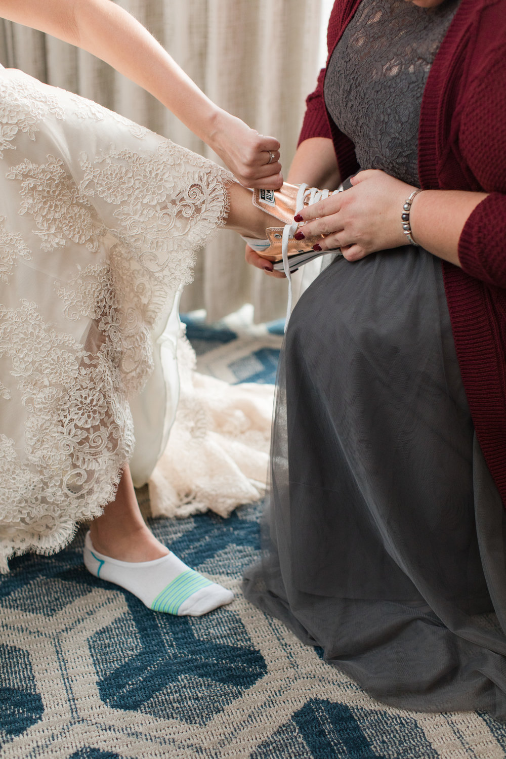 Maid of honor putting on bride's rose gold converse wedding shoes
