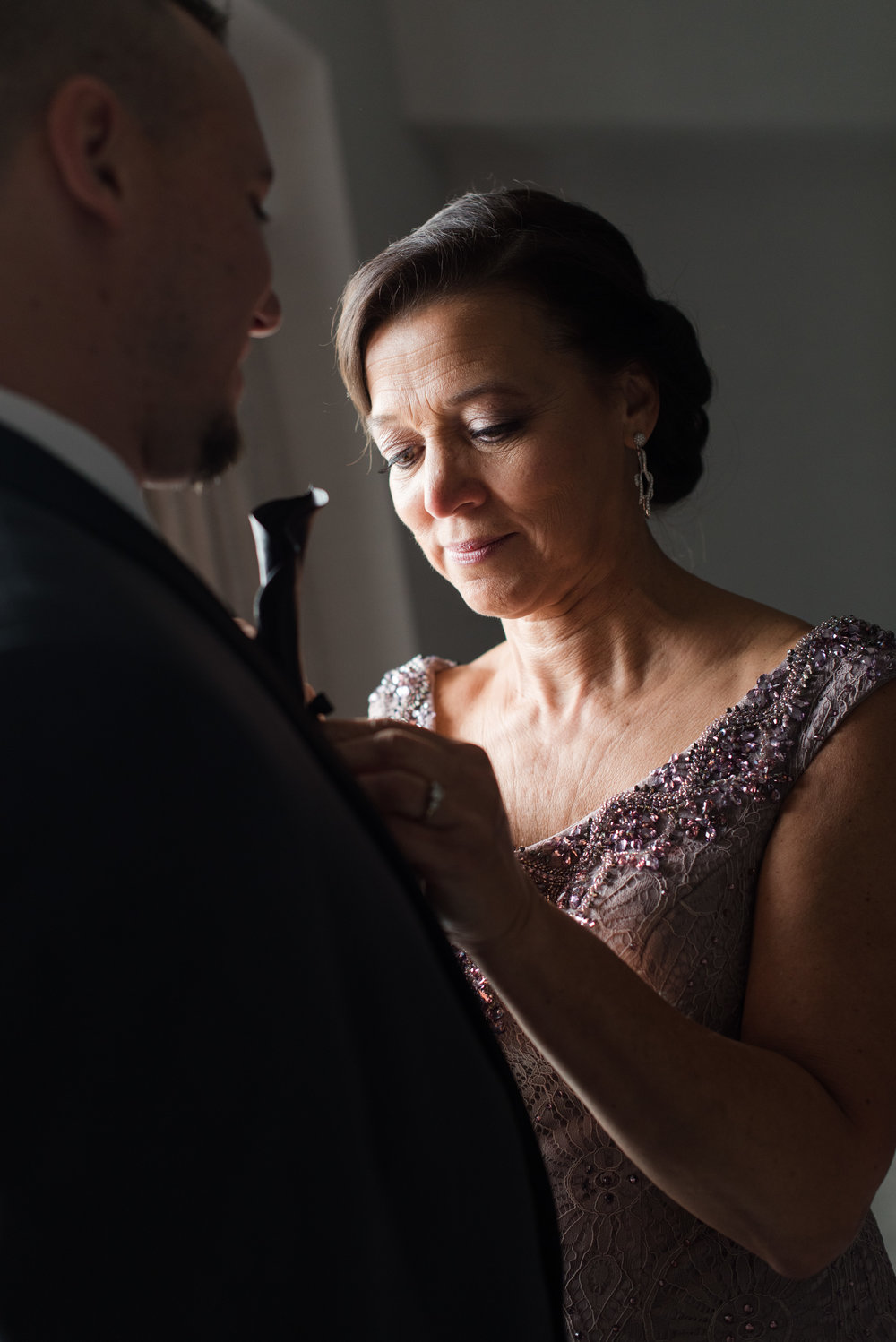Mother of the groom putting on calla lily boutonniere