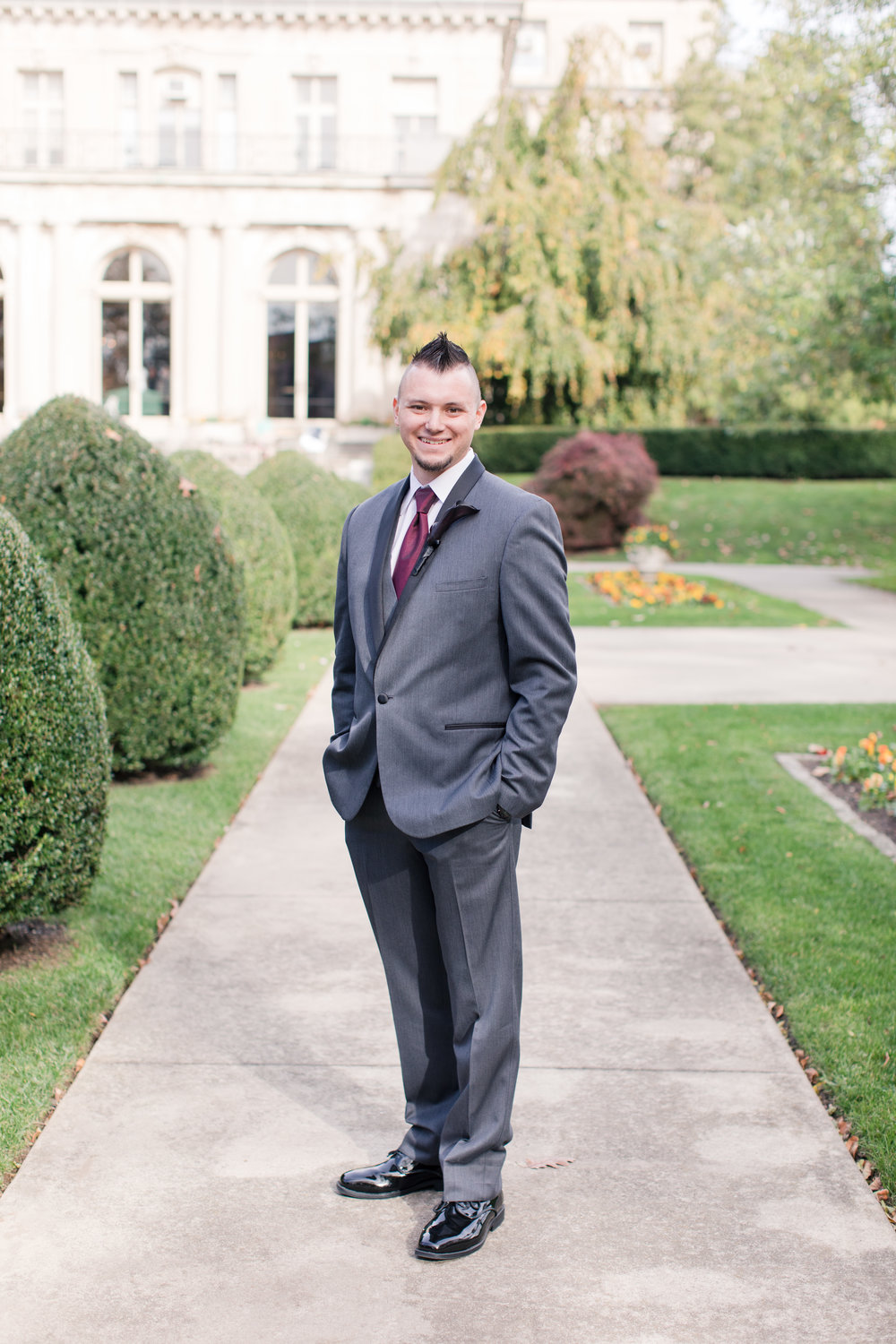 Groom in gray and black suit posing at Monmouth University