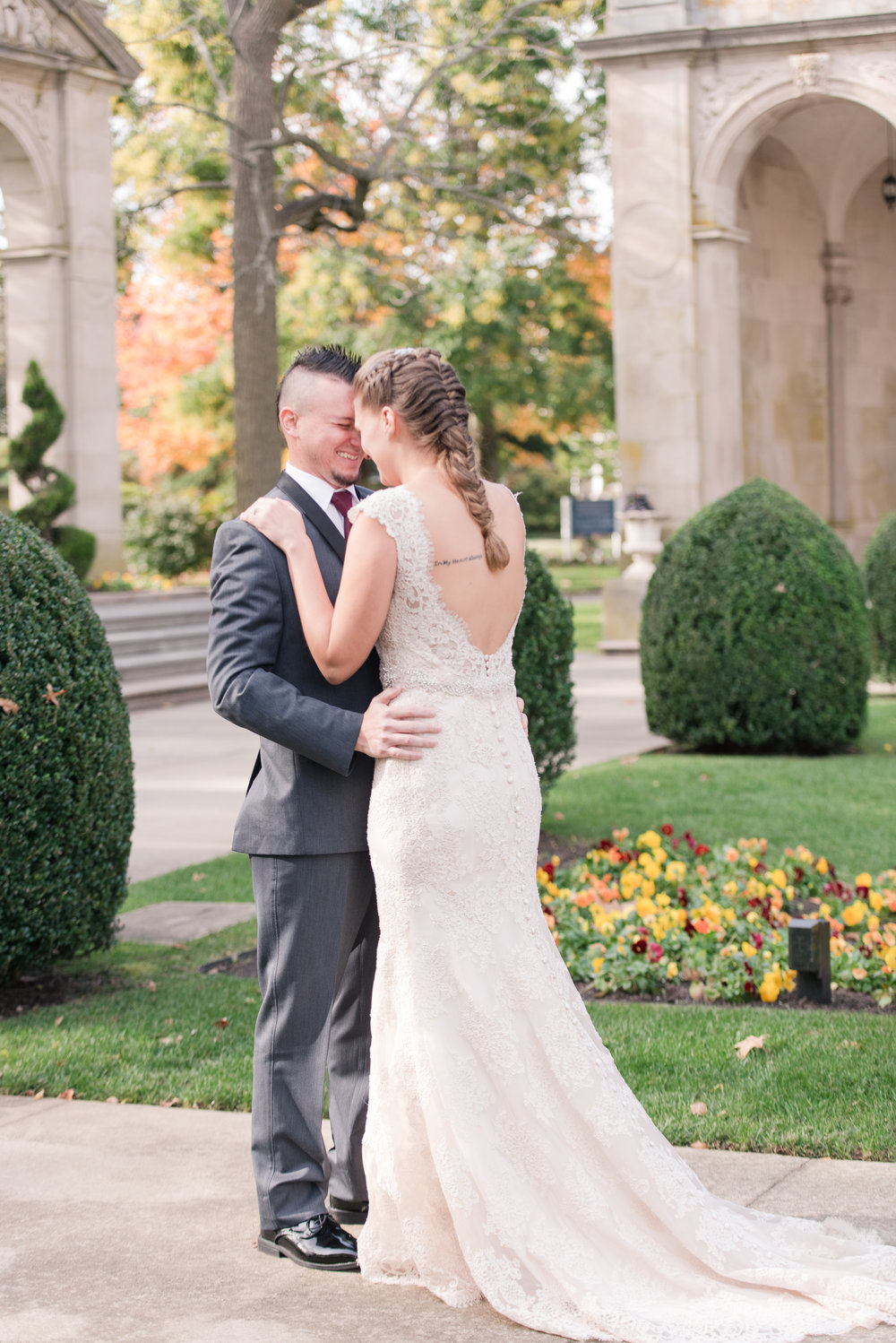 Groom in gray and black tux with bride in allure bridal lace gown with low back and buttons first look at Monmouth University