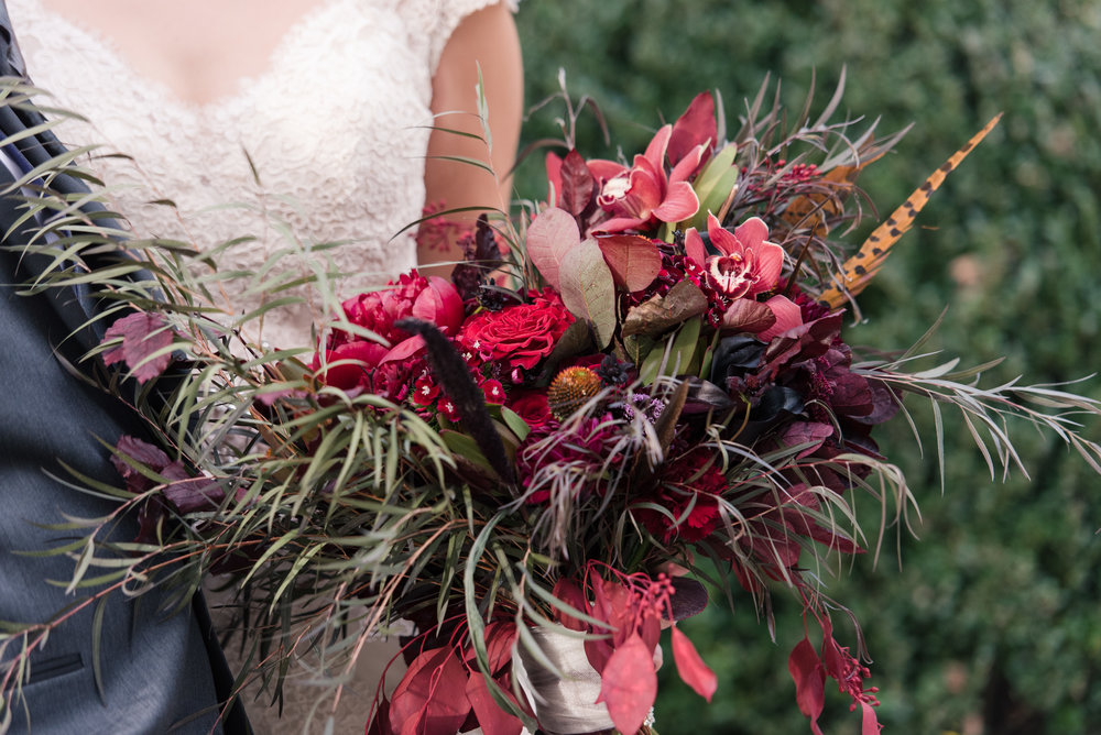 Deep red burgundy purple fall bridal bouquet with roses orchids and feathers