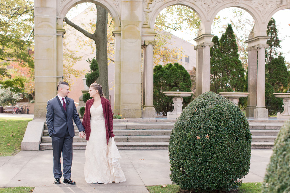 Monmouth University bride in allure bridal lace gown with red knit sweater walks with groom in black and gray tux