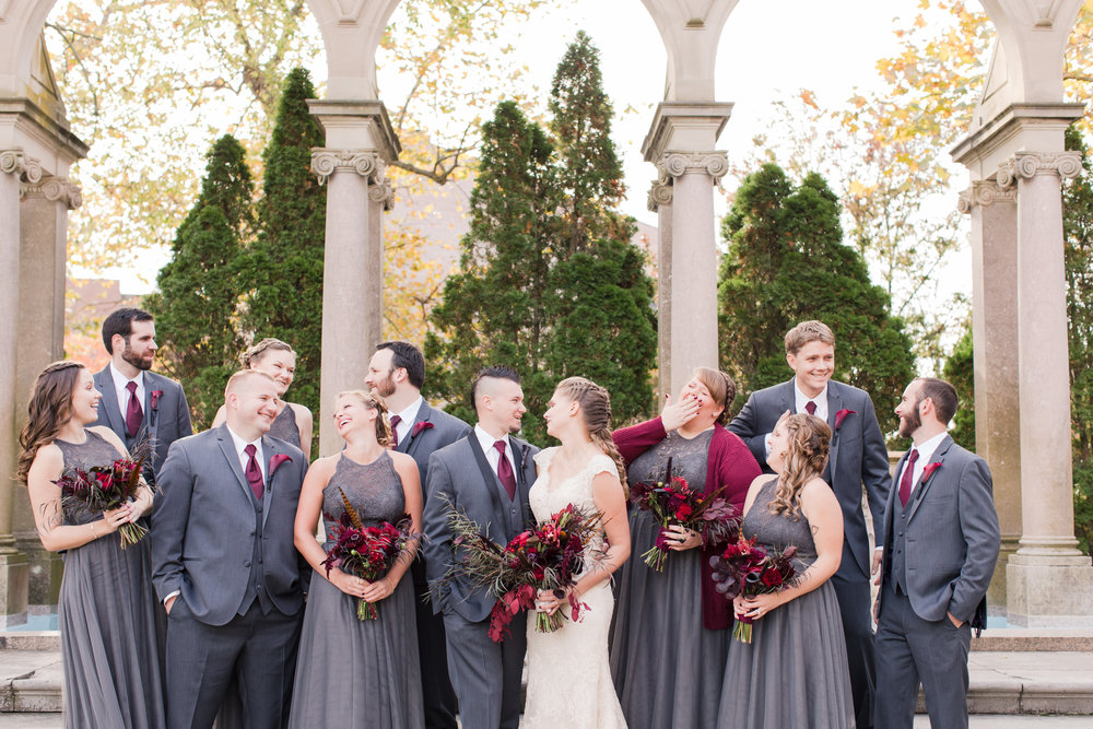 Fun bridal party photo at Monmouth University with charcoal gray dresses and dark red bouquets