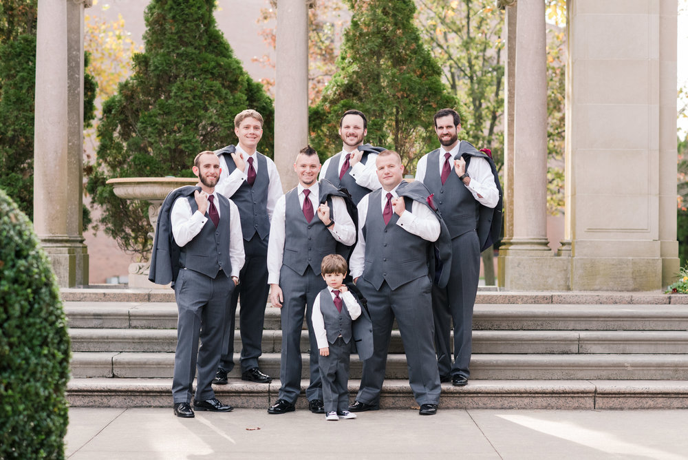 Groomsmen holding jackets in gray and black tuxes