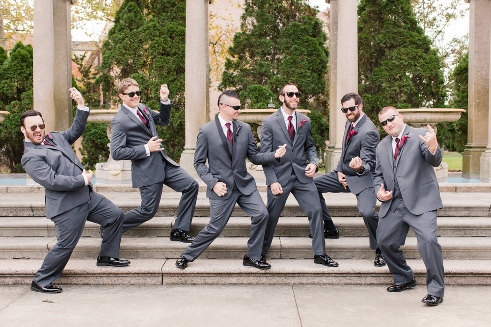 Groomsmen in dark gray suits take photo playing air guitar