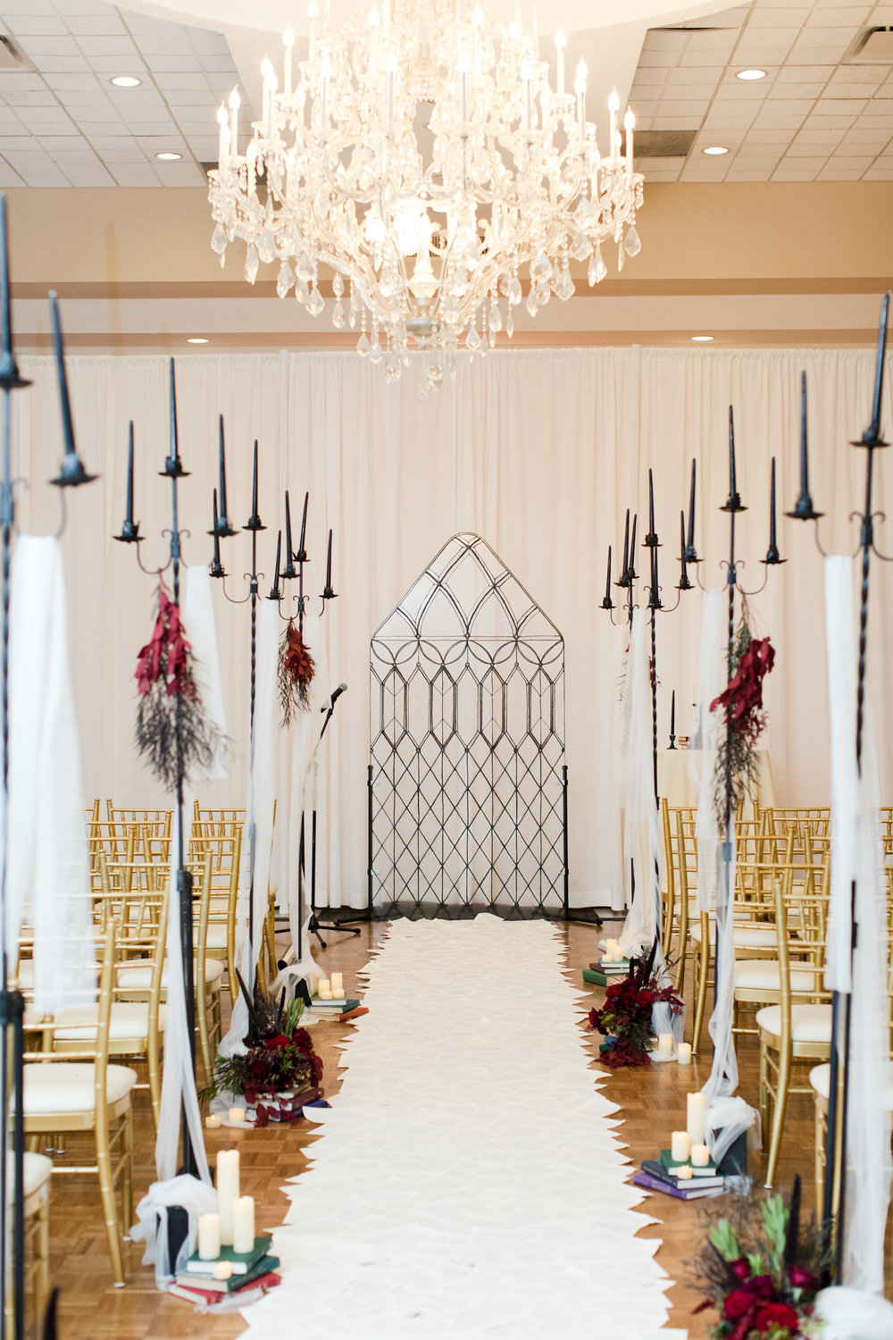 Book page aisle runner with seasonal fall floral atop books leading up to a castle window ceremony backdrop inspired by beauty and the beast for library inspired wedding at Buona Sera Palazzo