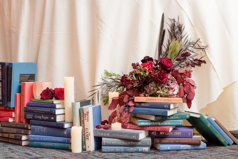 library inspired fall wedding sweetheart table with vintage books dark red fall flowers and candles