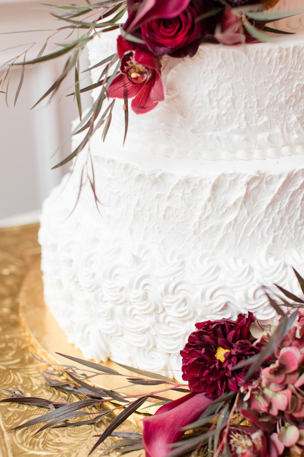 White wedding cake with dark red fall flowers