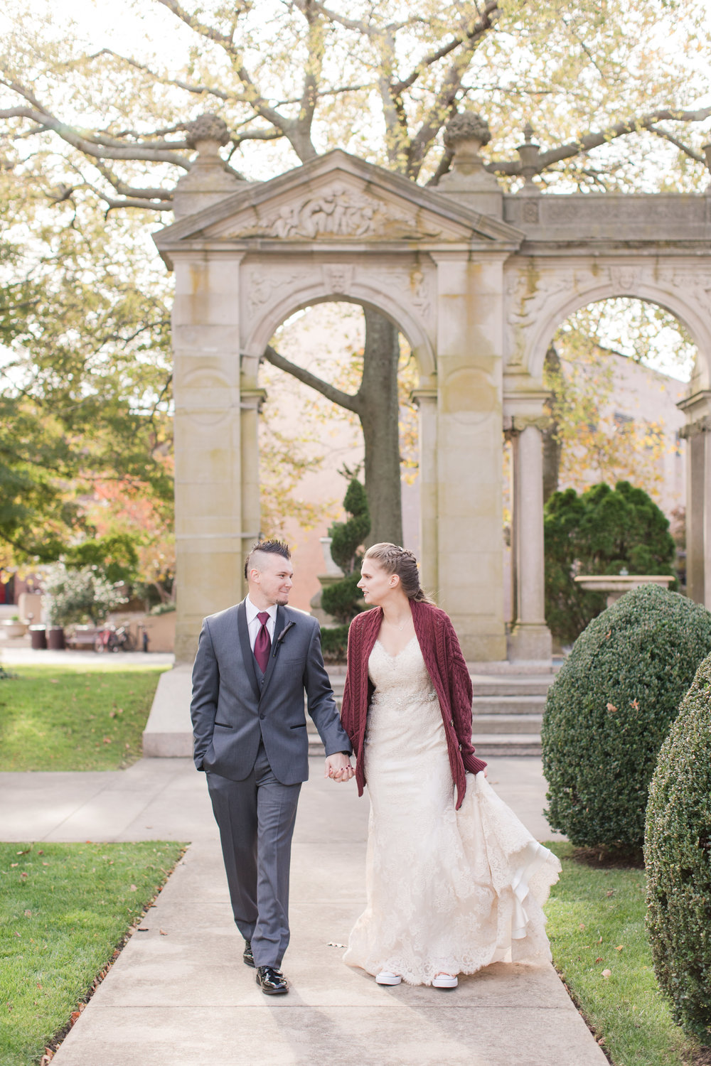 bride in lace allure bridal gown walks with groom wearing comfy sweater and rose gold converse