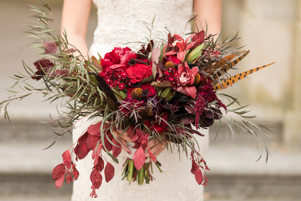 funky black and deep red bridal bouquet with whispy black leaves and feathers for alternative fall wedding