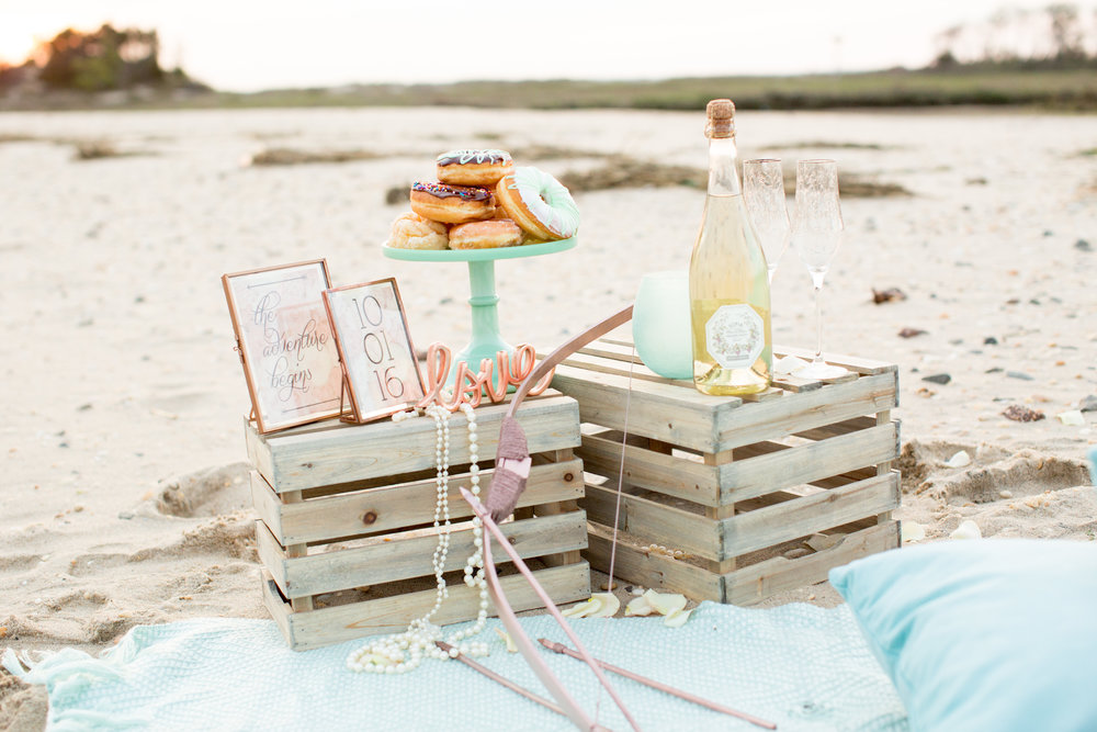 beach engagement photoshoot props at sandy hook including champagne and donuts for save the date ideas
