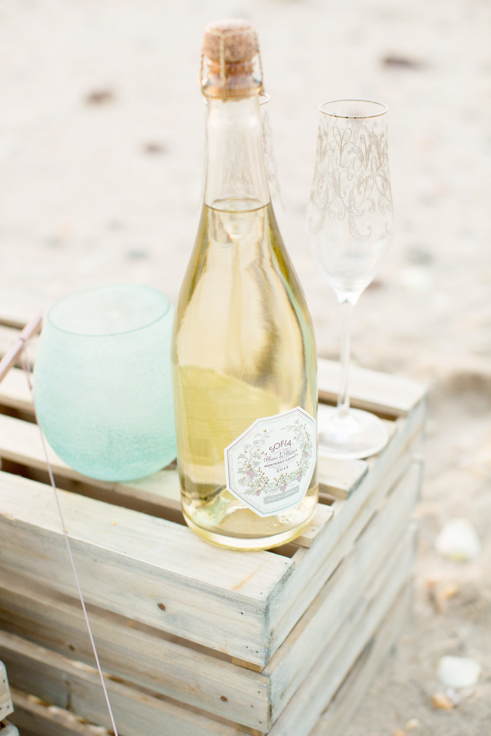 beach engagement photo shoot props and champagne