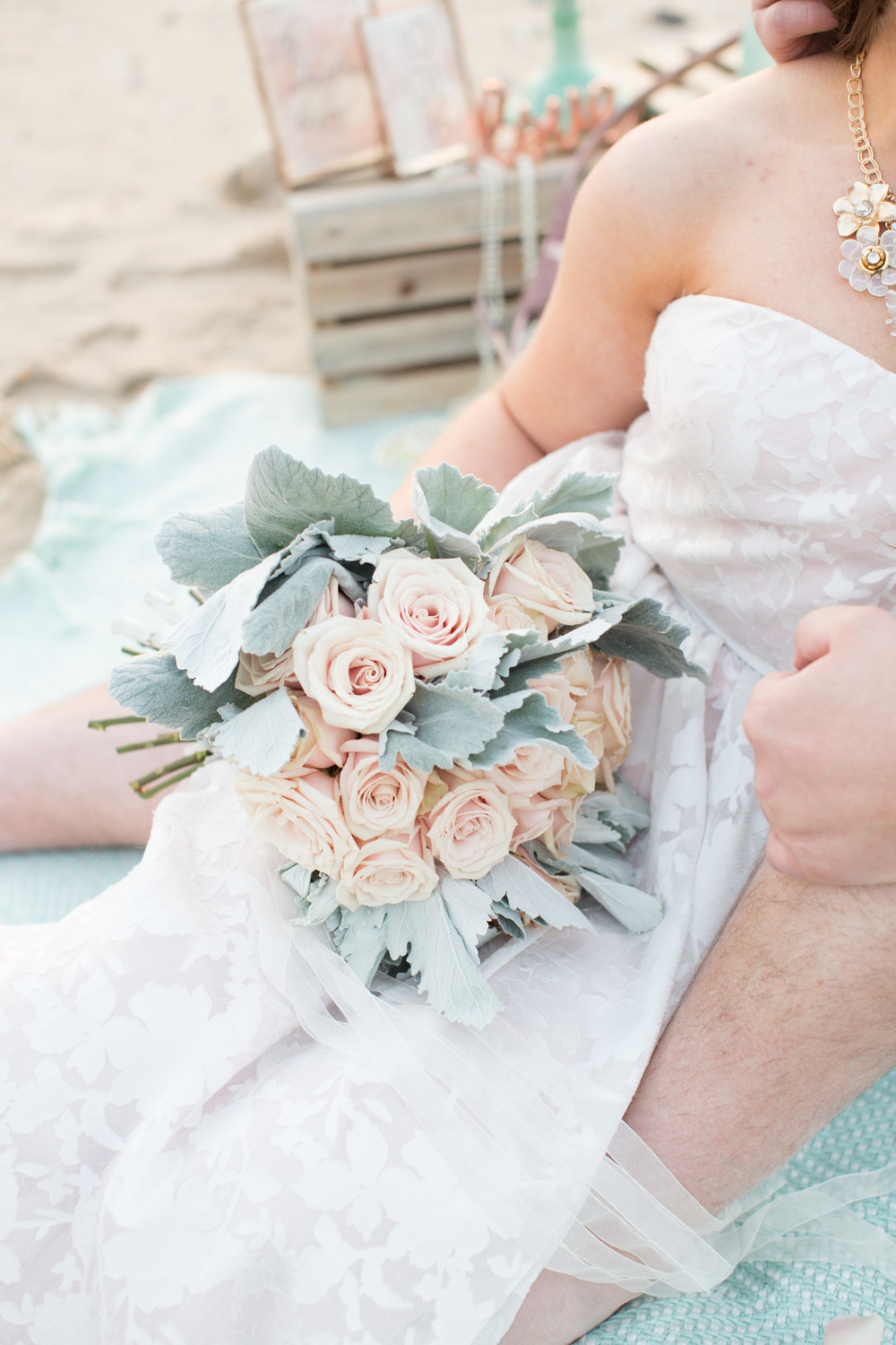 beach engagement photo shoot props with blush rose and dusty miller bridal bouquet for beach wedding