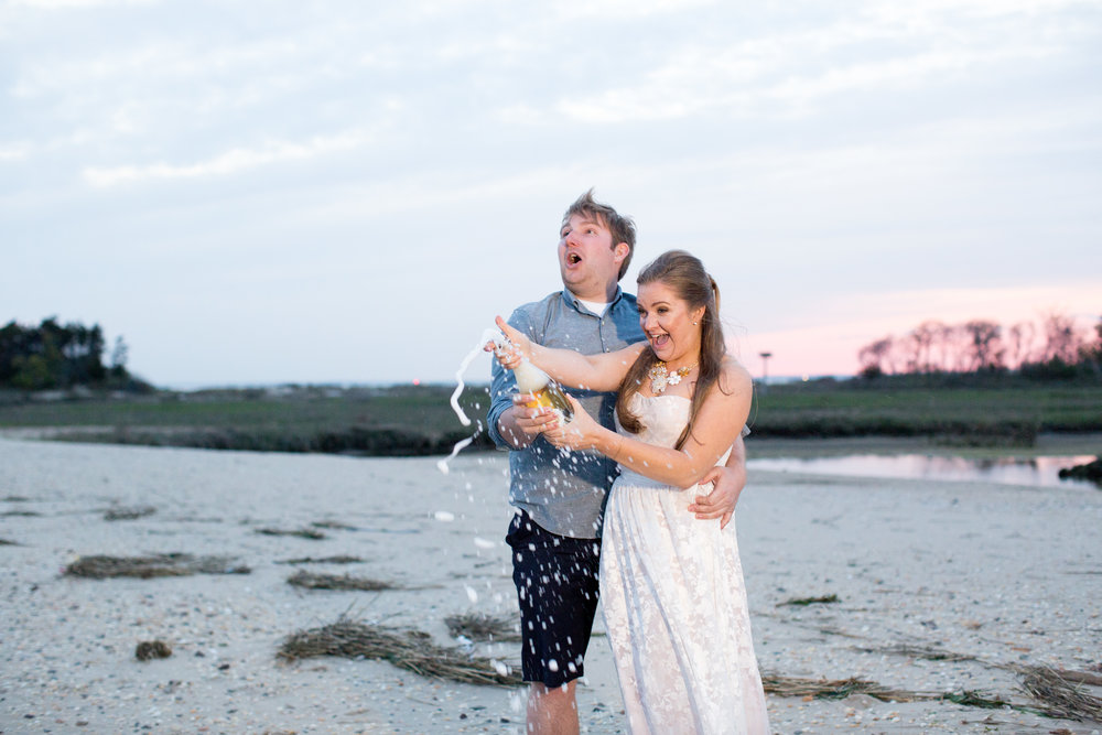 pop champagne photo at beach engagement at sandy hook at sunset with jaye kogut photography