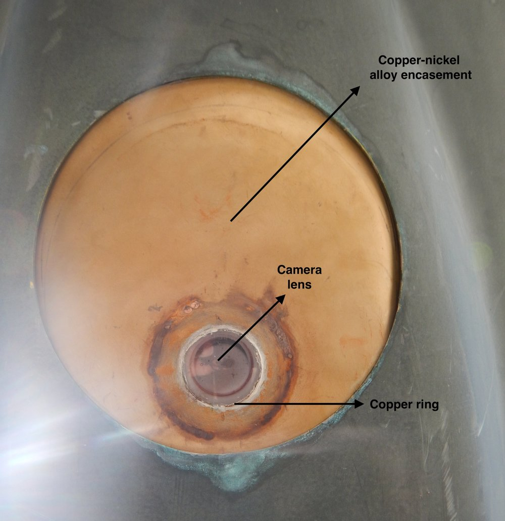 This image displays the bottom of Europa's float, painted with a Coopercoat paint. The Camera (facing down) is encased in a copper-nickel alloy housing with an additional copper ring around the acrylic lens to prevent biofouling.