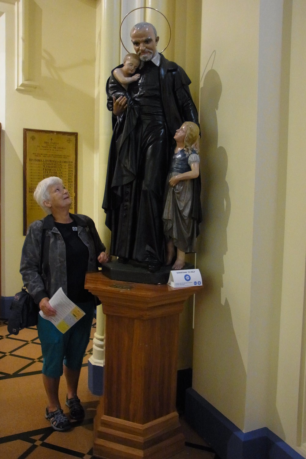 Steph at St Mary's of the Angels with a statue of St Vincent de Paul.