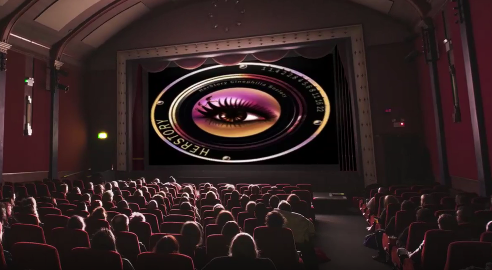 Theater with Audience and Logo on Screen.PNG