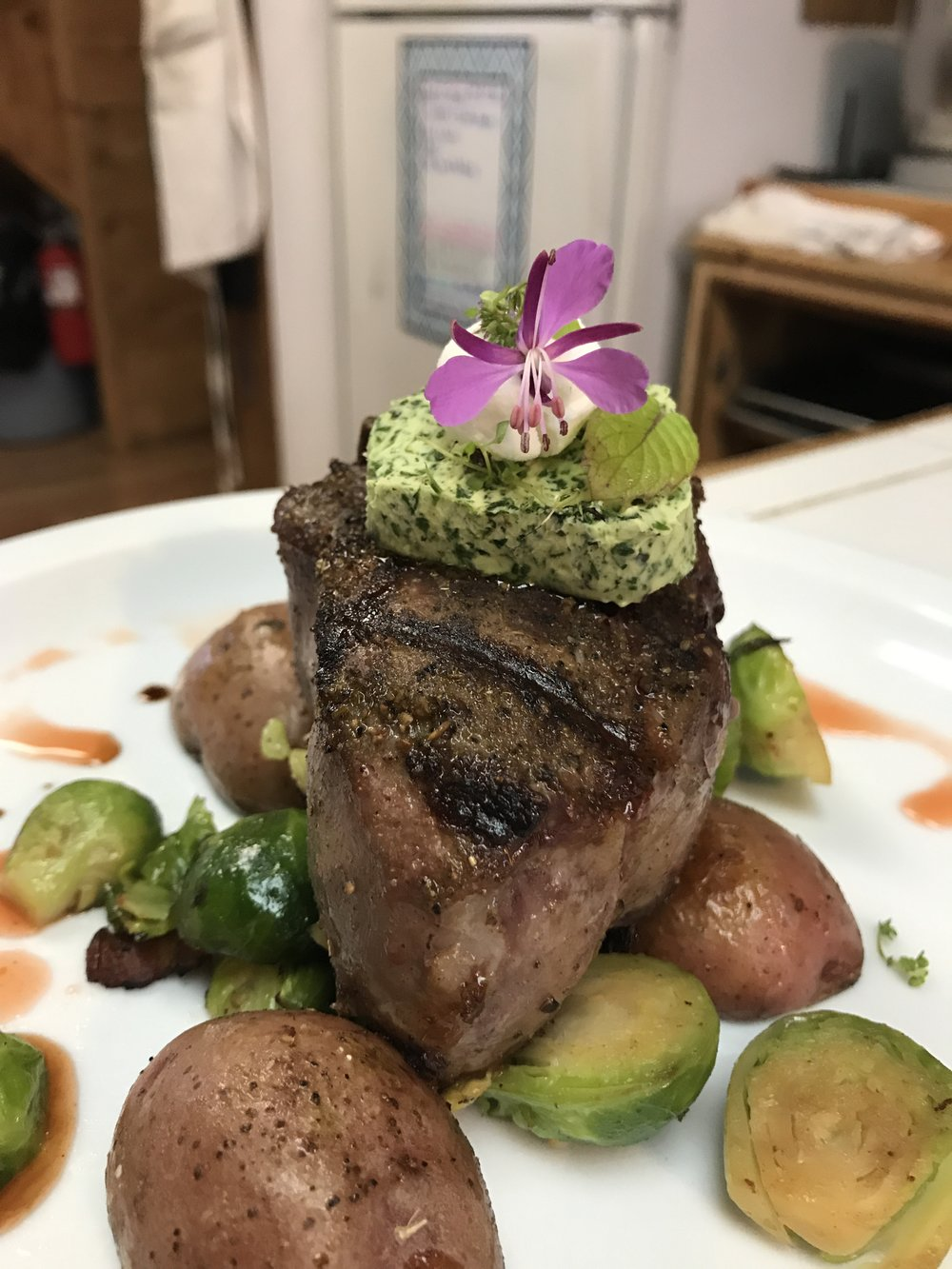 Grilled Lamb topped with Herb Butter over Roasted Red Potatoes and Brussels Sprouts, garnished with wild Fireweed.