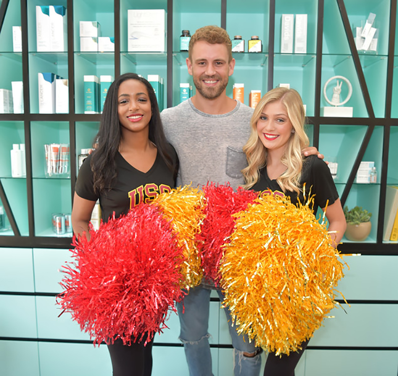"""Former """"Bachelor """" star Nick Viall poses with USC song girls at the facial bar's grand opening in USC Village."""