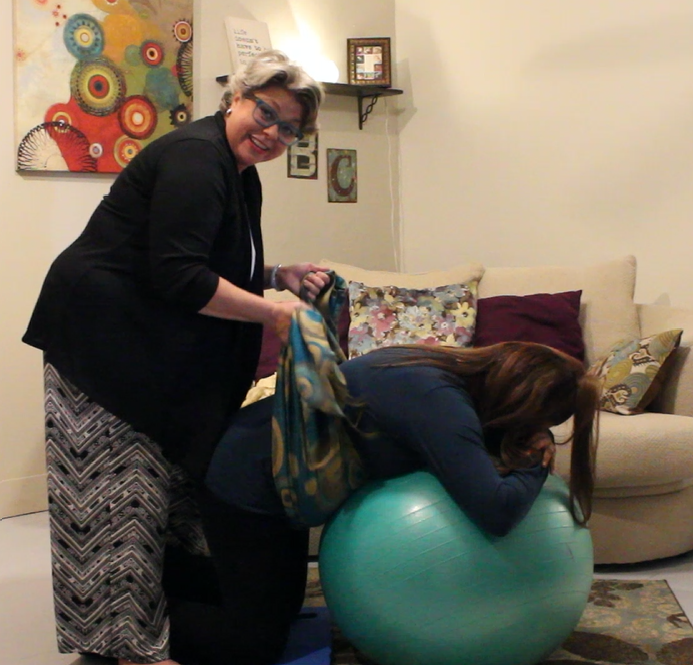 Brenda  demonstrating hands-on techniques to help the mother stay more relaxed, promoting the hormones that keep labor moving smoothly with Rebozo sifting.