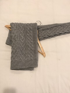 - Fold body of sweater over hanger