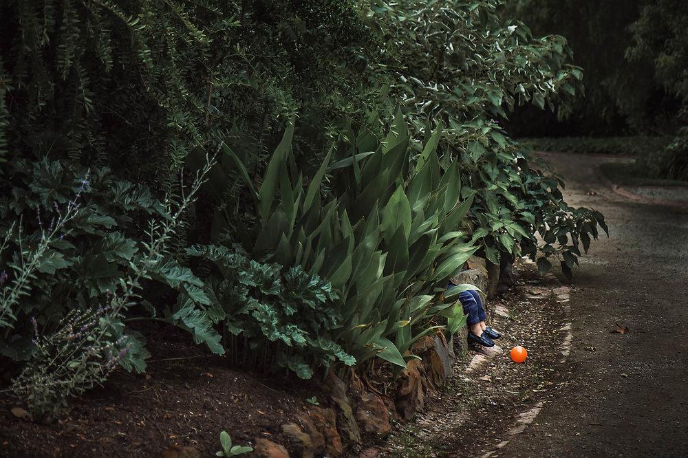 friendsless_boy_alone_garden_orange_ball_waiting_friend_annick_simon_photographe_famille_quebec.jpg