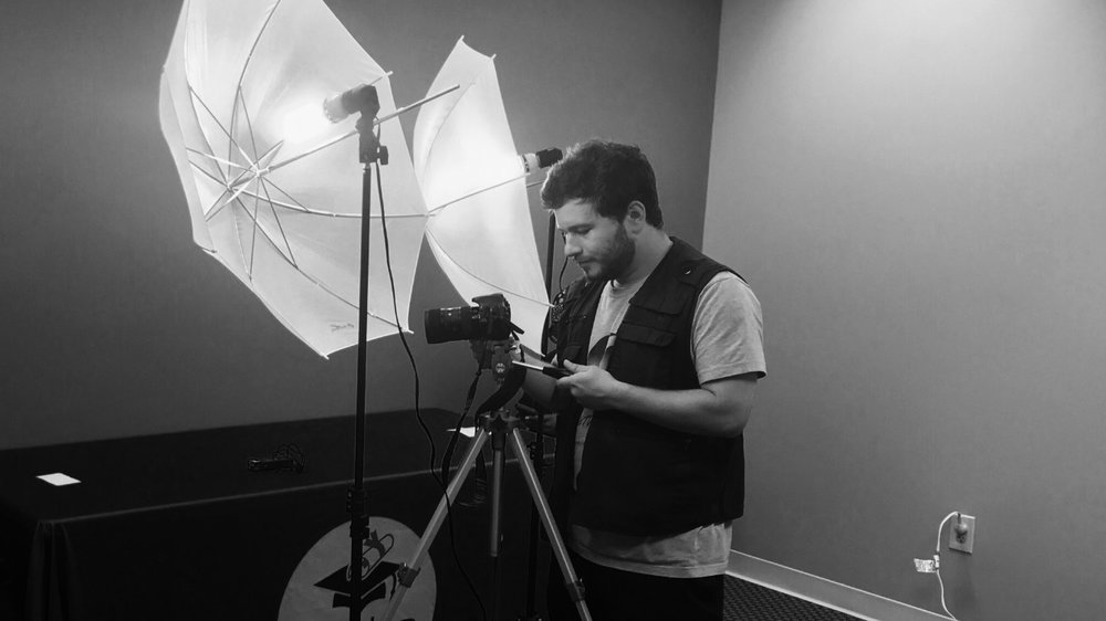 Conor Mitchell setting up camera and lighting angles while filming interviews for the Fasko Education Scholarship Program.