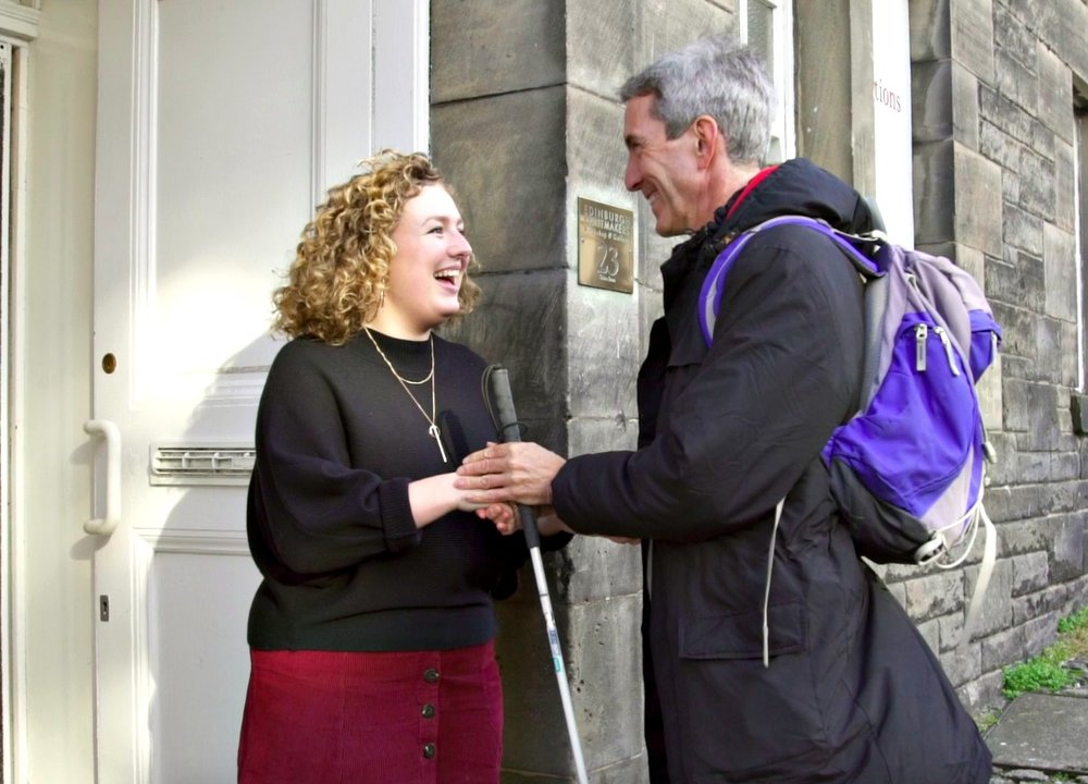 Ken being greeted with a handshake by Molly, receptionist at Edinburgh Printmakers.