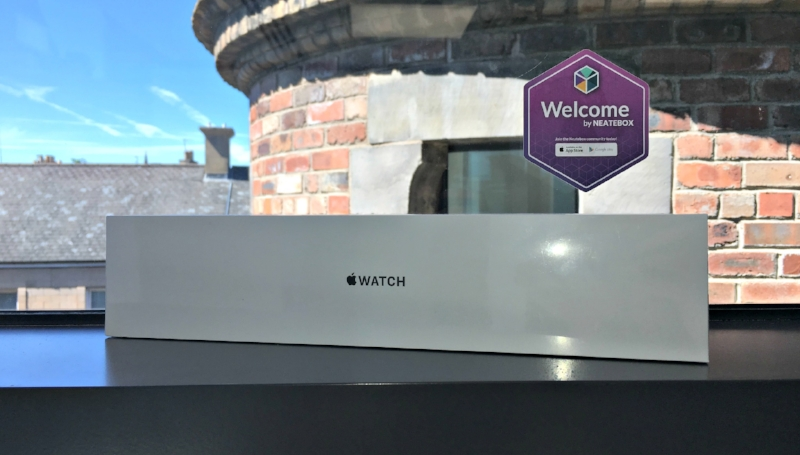Apple Watch in its box on a window sill with a Welcome sticker behind