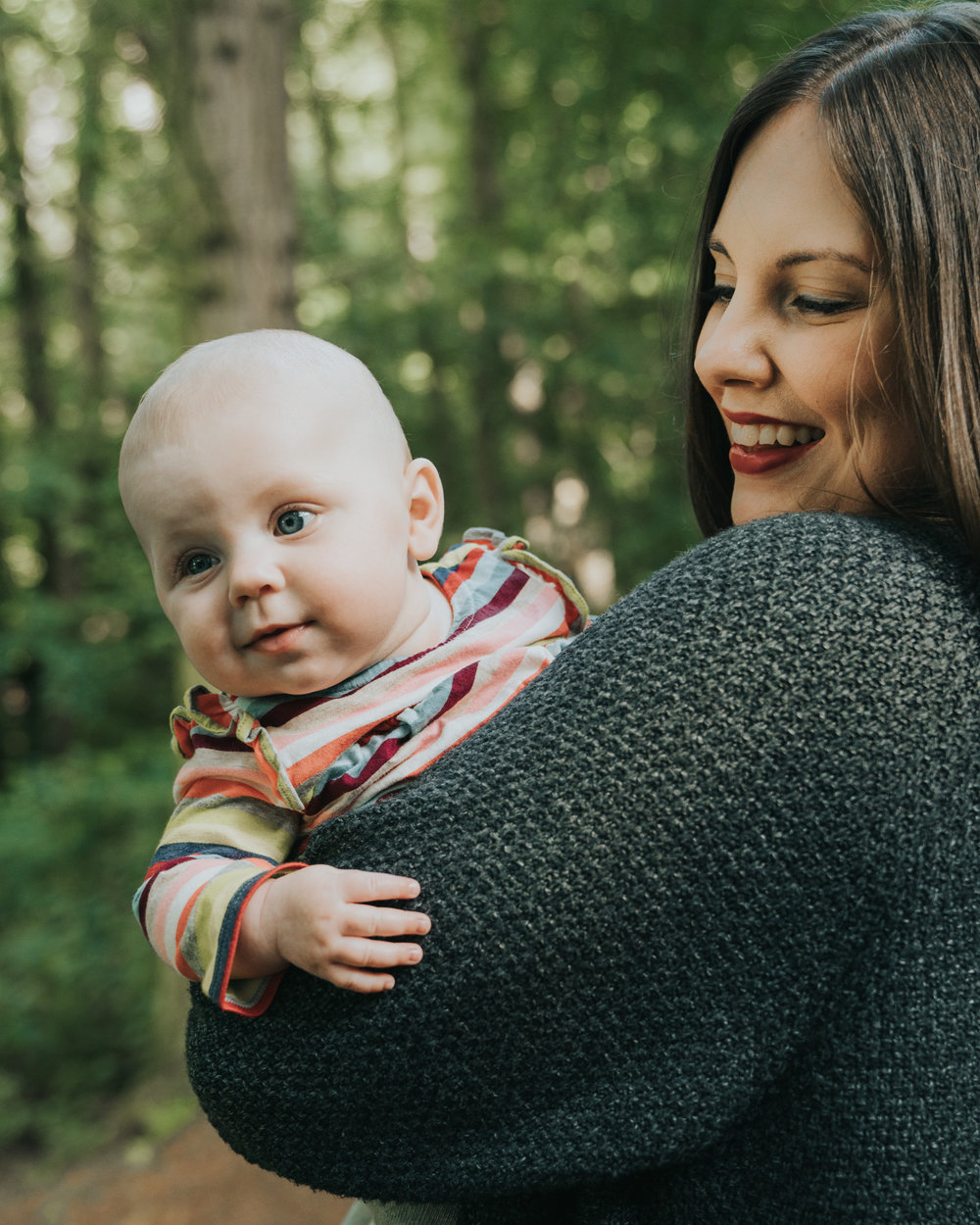 Mother and baby daughter cuddle at forest family session in Suffolk