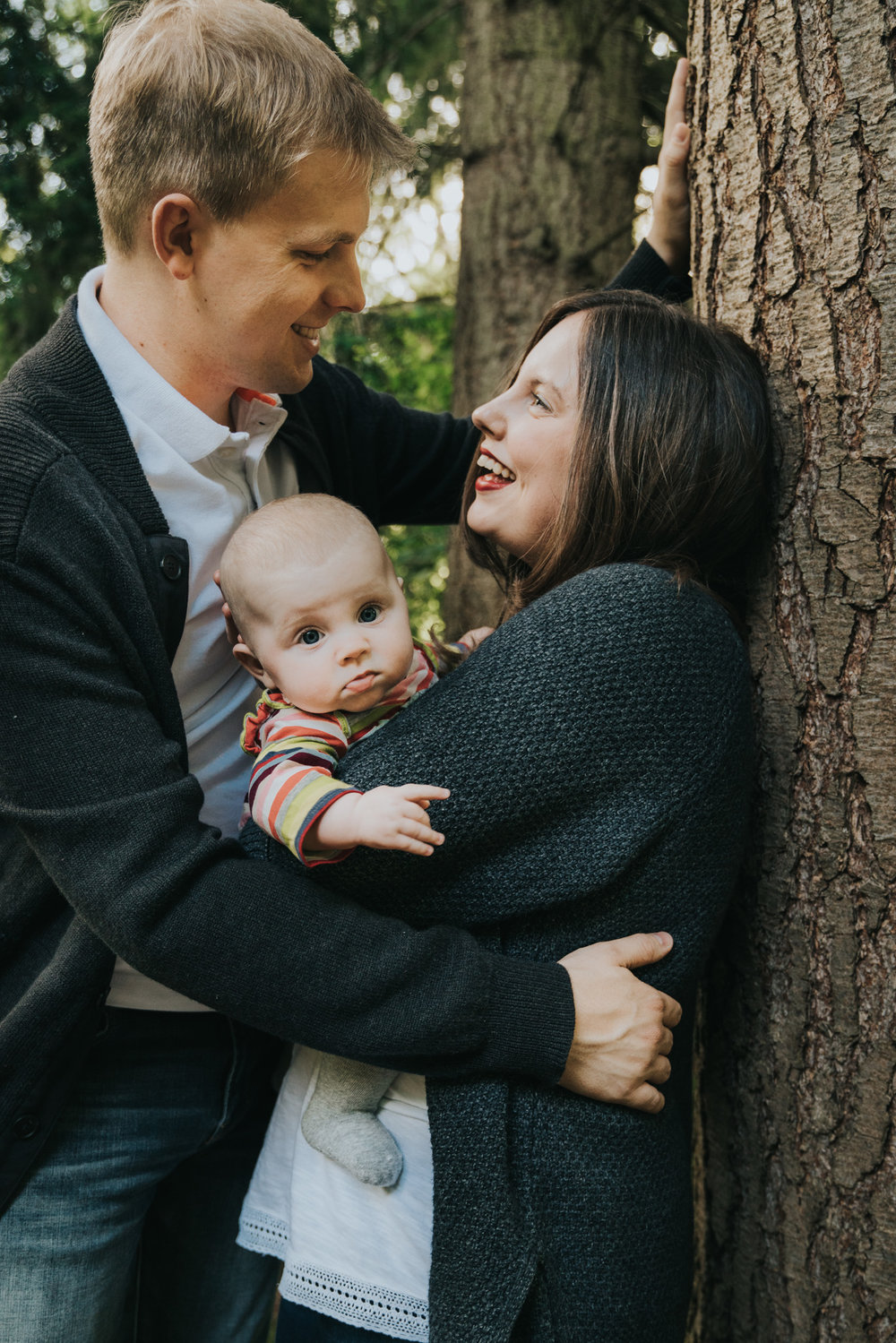 Family cuddle together next to a tree at forest family session in Suffolk