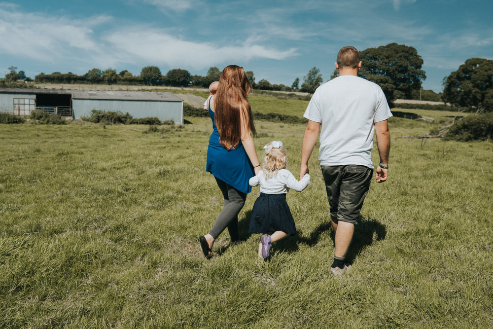 Family session on location, family walking through North Devon farm field