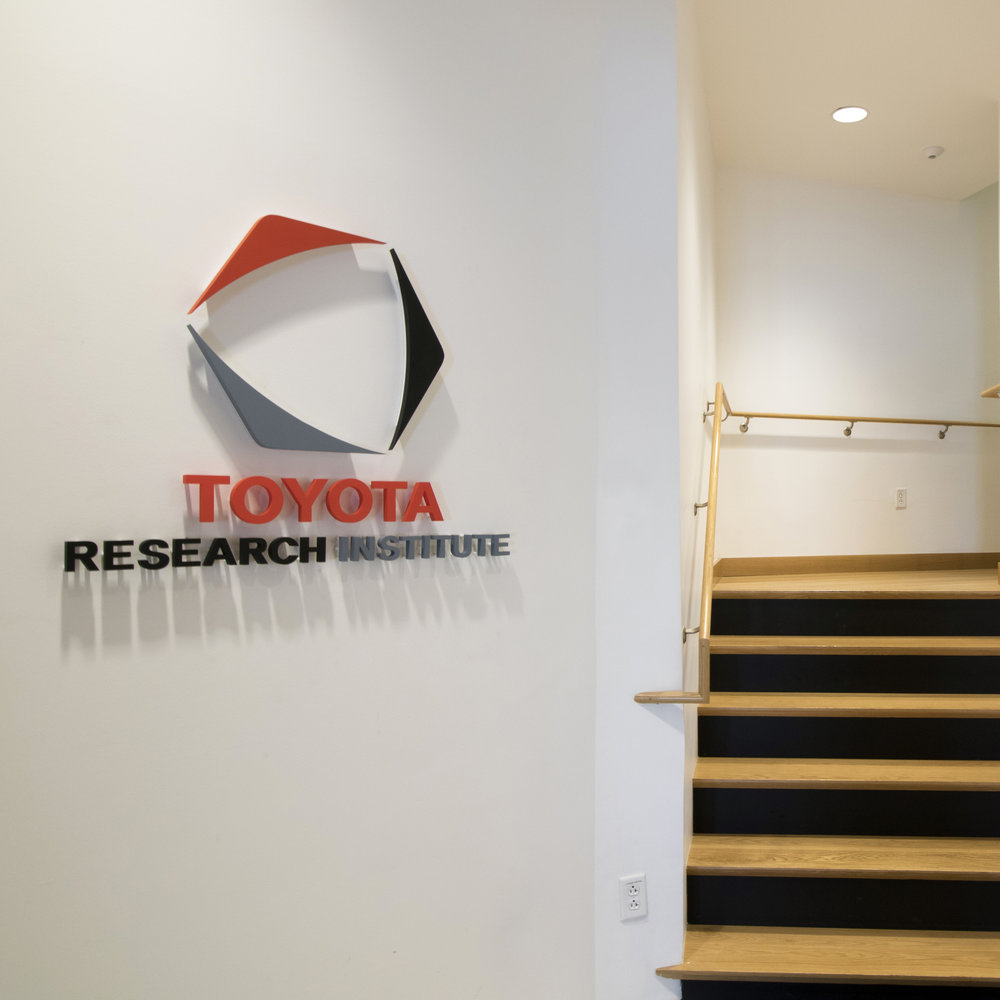 Toyota Research Institute Environmental Graphics and Signage   From the front entry doors to the corner tower, this way-finding package includes all room identification signs and playful restroom graphics, and helps to define an aesthetic for the new Toyota Research Institute in the heart of Cambridge.