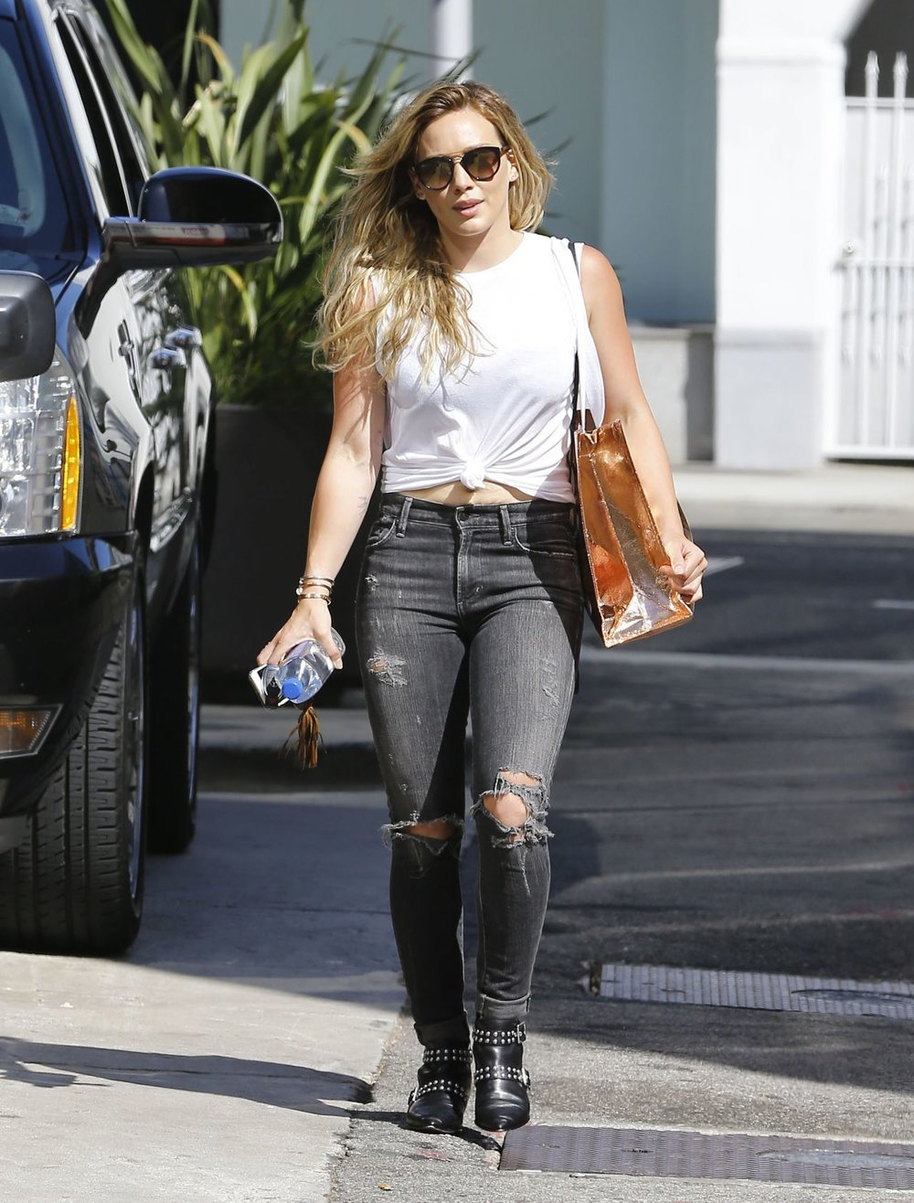 Hillary Duff - makes casual look so easy. She paired her knotted tank with a pair of ripped up dark denim.