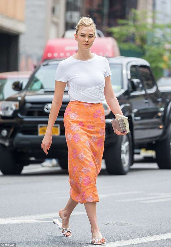 Karlie Kloss - Karlie Kloss mixes her bold midi skirt with a cool tee and flat sandals for a laid back summer look.