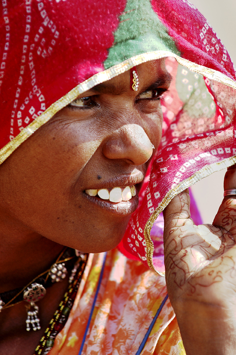 Travel Image ~ Lady In Red - Osiyan, IndiaThe bleak deserts of Rajasthan create a canvas for women dressed in intense hues to splash the landscape with bursts of color.   This woman outside the small town of Osiyan lights up in red.  She is a new bride, as indicated by the red sari she adorns and the intricate henna designs on her hand. The henna adornment signifies the strength of love in a marriage.  No matter where a woman resides in the world she a being of shakti…the power that links and births us all.