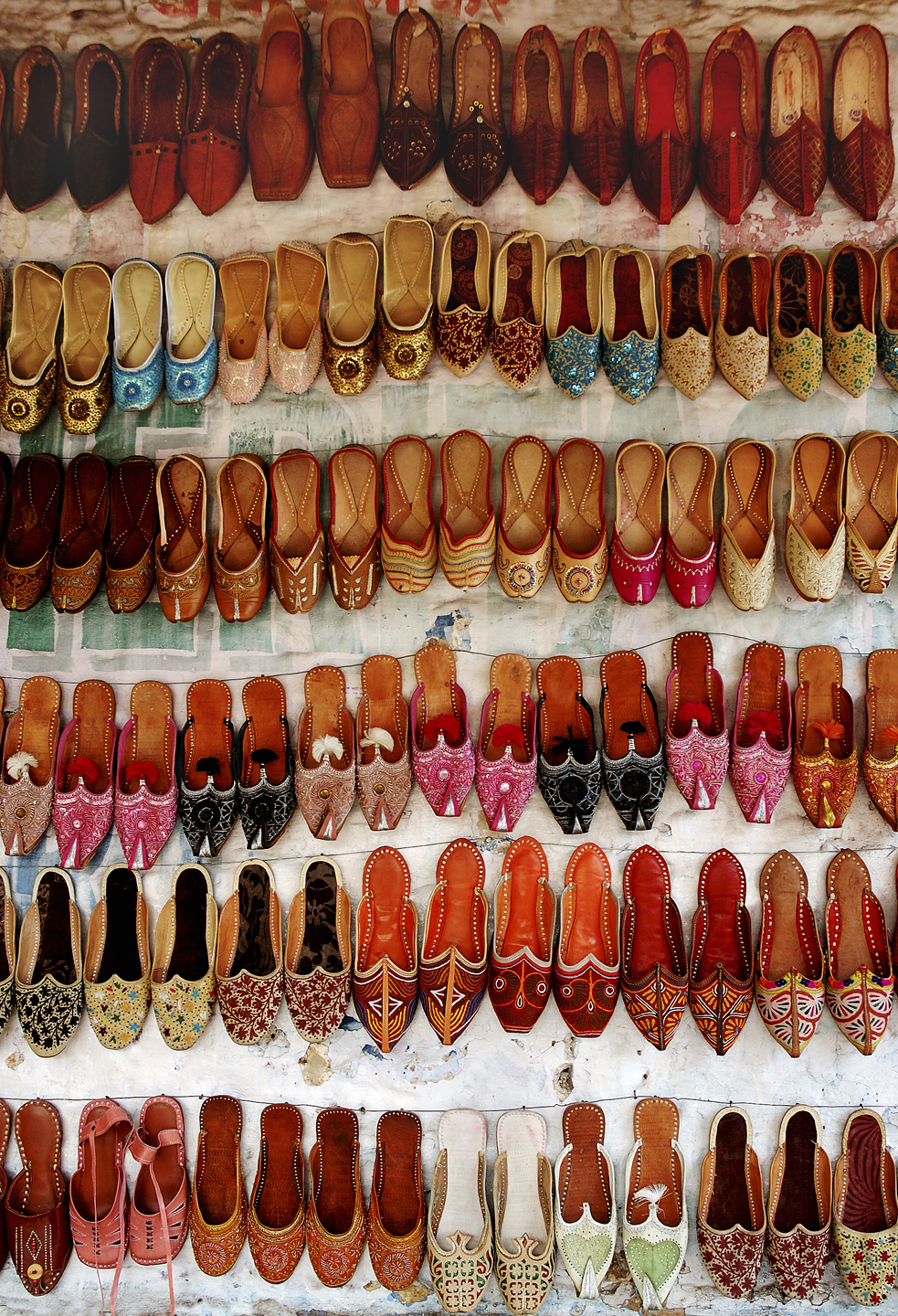 Travel Image ~ Rajasthani Shoes - Jodhpur, IndiaThe town center of Jodhpur, in the heart of Rajasthan, teems with the hustle of markets around the world.  Spices are measured for sale in one corner with shoes in the next corner.  The traditional designs on these shoes are often hand stitched in local homes.  The young man selling these shoes swore they were stitched by his own mother.  Here, you can walk away wearing a little piece of the India of the maharajas.  These shoes remind me of all the different shoes we wear & the diverse paths we walk each lifetime.