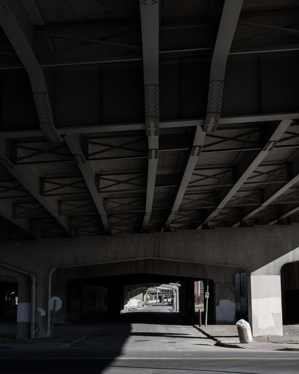 While there is not always a lot of color in a concrete environment, I reduced the saturation of what color there is in this image to emphasize the play of light and shadow under the overpass