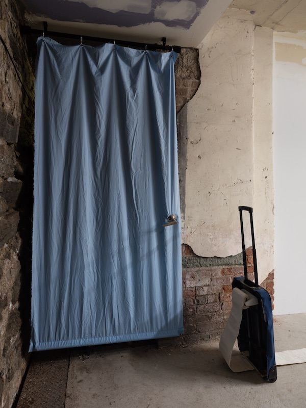 Chris Zacher  Blue door , 2018 Bed sheet, door handle, aluminum, wood, shower curtain rings and hardware 38 x 82 inches & Chris Zacher  Unfinished bathroom , 2018 Rolling suitcase, shoe, papier-mâché, toilet paper holder and hardware 125 x 14 x 43 inches