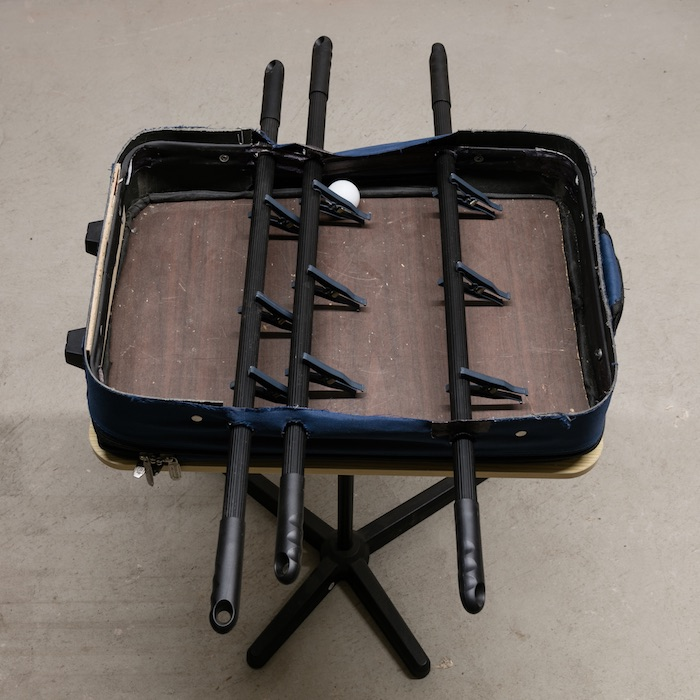 Chris Zacher  Foosball table , 2018 Table, suitcase, wood, broom handles, clothespins and ping pong ball 30 x 22 x 30 inches