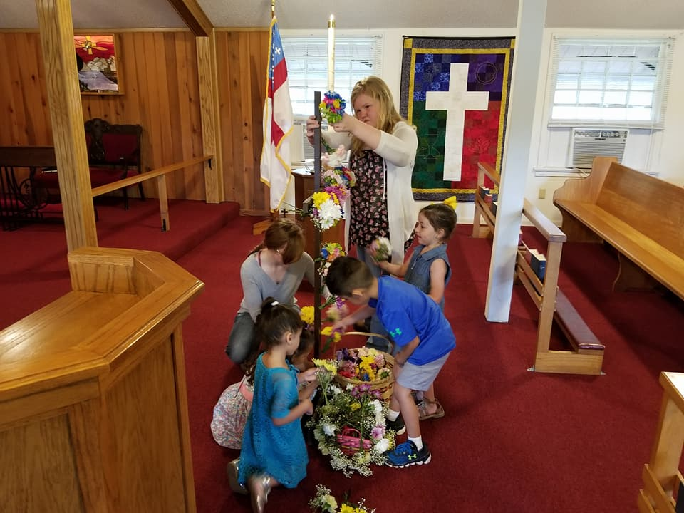 Children flowering the cross on Easter Sunday.