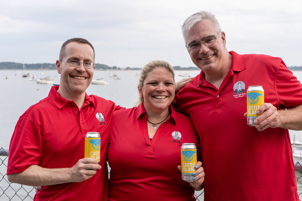 Mark Howley (volunteer wrangler), Elaine Howley (race director) and Greg O'Connor (race director) constitute the core event team for the Boston Light Swim. Photo from the 2018 event's pre-race dinner, with thanks to our sponsor, Castle Island Brewing Company for their generous (and tasty) donation.   Photo by Jon Washer