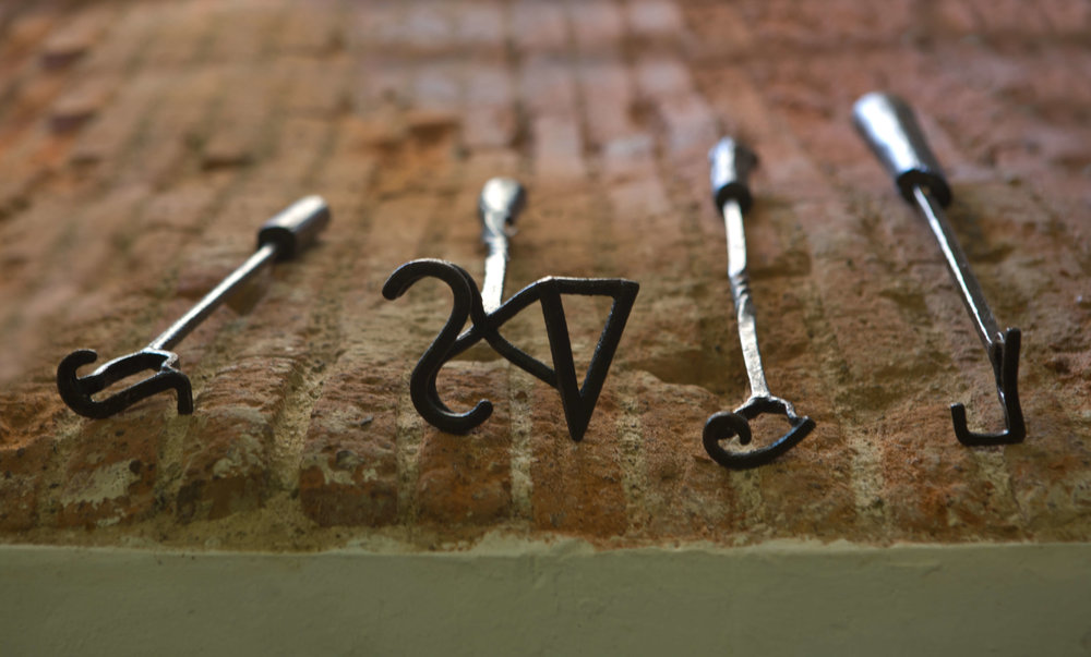 Branding irons displayed on brick