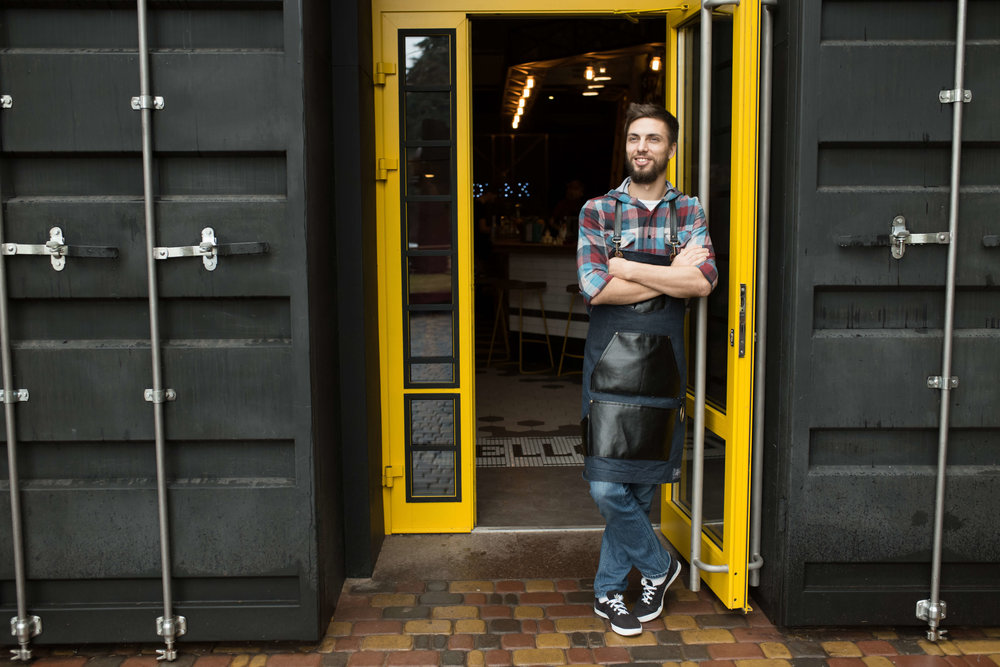 Man in apron in front of restaurant built from shipping containers