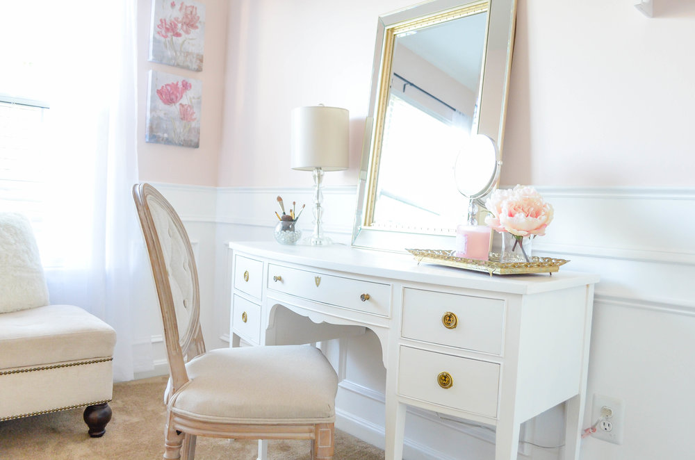 Sherwin Williams Intimate White (SW 6322). This elegant Parisian inspired Beauty Room is the perfect retreat for the lady of the house to escape with a glass of wine or a pot of tea. The impeccable white wainscoting compliments the soft pink walls and Parisian style decor. A perfectly placed white vanity makeup table adorned with a soft gold beveled mirror is the perfect place to apply those finishing touches for a night out on the town!